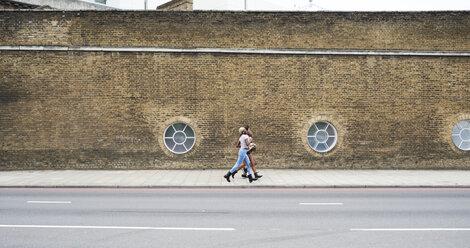 Three friends walking on pavement - IGGF00110