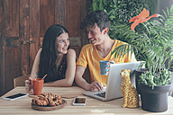 Young couple having coffee and chocolate braids using laptop at home - RTBF00994