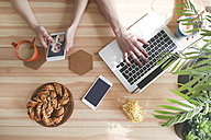 Young couple having coffee and chocolate braids using laptop and smartphone, top view - RTBF00997