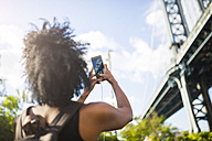 USA, New York City, Brooklyn, woman taking cell phone picture of Manhattan Bridge - GIOF03085
