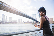 USA, New York City, Brooklyn, woman listening to music near Manhattan Bridge - GIOF03091