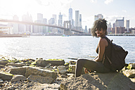 USA, New York City, Brooklyn, portrait of smiling woman sitting at the waterfront - GIOF03097