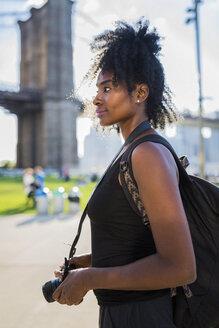 USA, New York City, Brooklyn, woman with camera at Brooklyn Bridge - GIOF03109