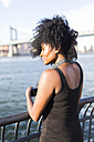 USA, New York City, Brooklyn, woman standing at the waterfront - GIOF03112