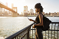 USA, New York City, Brooklyn, woman with cell phone standing at the waterfront - GIOF03115