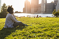 USA, New York City, Brooklyn, woman sitting on meadow looking at the skyline - GIOF03118