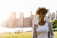 USA, New York City, Brooklyn, smiling woman standing on a meadow - GIOF03121