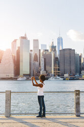 USA, New York City, Brooklyn, woman standing at the waterfront taking cell phone picture - GIOF03130