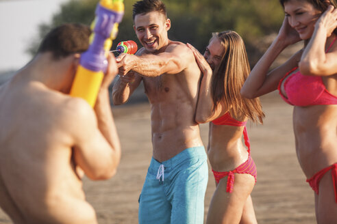 Happy friends playing with water guns on the beach - VPIF00010