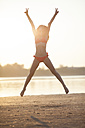 Happy young woman jumping on the beach - VPIF00019