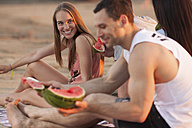 Happy couple with friends on the beach eating water melon - VPIF00022