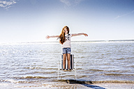 Netherlands, Zandvoort, girl standing on chair in the sea with outstretched arms - FMKF04309