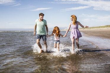 Netherlands, Zandvoort, happy family splashing in the sea - FMKF04312