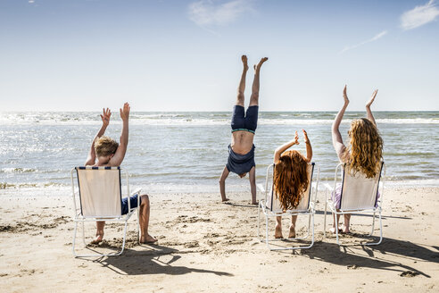 Netherlands, Zandvoort, family clapping hands for father doing a handstand on the beach - FMKF04315