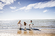 Netherlands, Zandvoort, family sitting on chairs in the sea - FMKF04318