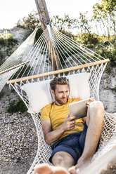 Man lying in hammock using tablet - FMKF04321