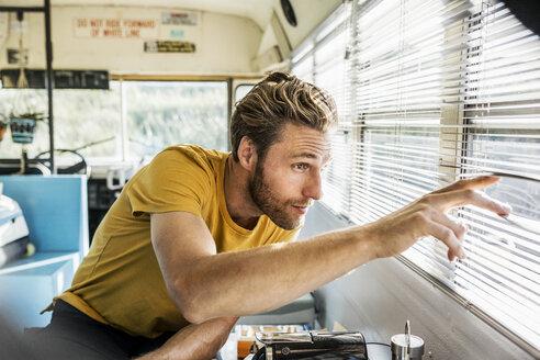 Man in an old bus peeking through sunblind - FMKF04324