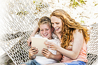 Happy mother and son in hammock looking at tablet - FMKF04333