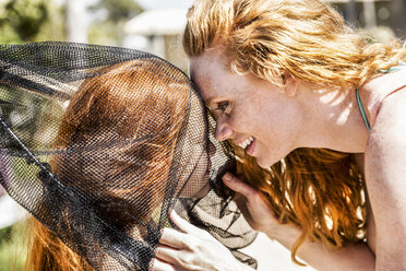 Happy redheaded mother and daughter in net - FMKF04339