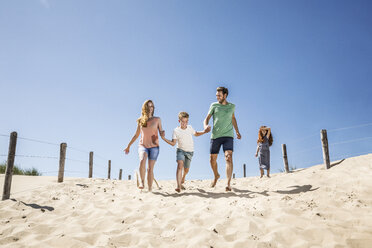 Netherlands, Zandvoort, happy family running on the beach - FMKF04345