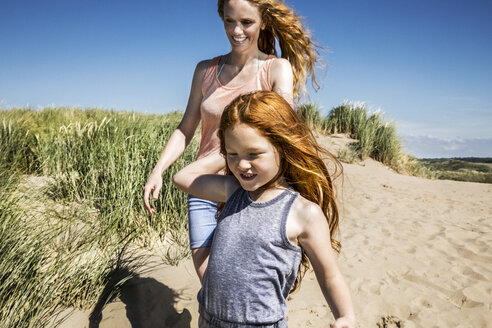 Netherlands, Zandvoort, happy mother and daughter walking in beach dunes - FMKF04348