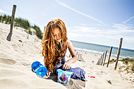 Netherlands, Zandvoort, redheaded girl playing on the beach - FMKF04351