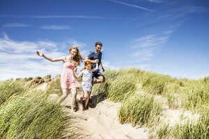 Netherlands, Zandvoort, happy family with daughter running in beach dunes - FMKF04360