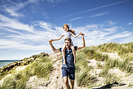 Netherlands, Zandvoort, father carrying daughter on shoulders in beach dunes - FMKF04366