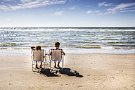 Netherlands, Zandvoort, boy and girl sitting on chairs on the beach - FMKF04369