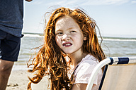 Netherlands, Zandvoort, portrait of redheaded girl on the beach - FMKF04375