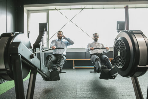 Businessmen training in gym, while making a phone call - JOSF01318