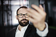 Portrait of an ambitious businessman, taking a selfie - JOSF01324