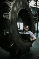 Businessman sitting in truck tire in a gym, using laptop - JOSF01336