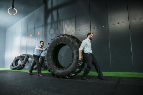 Two businessmen pushing and pulling truck tire - JOSF01339