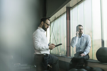 Two businessmen having a meeting in office - JOSF01357