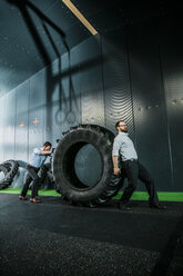 Two businessmen pushing and pulling truck tire - JOSF01360