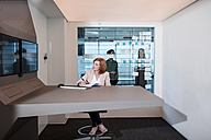 Businesswoman working in futuristic office looking at screen - ZEF14306