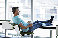 Businessman sitting in office with feet up, holding digital tablet - ZEF14321