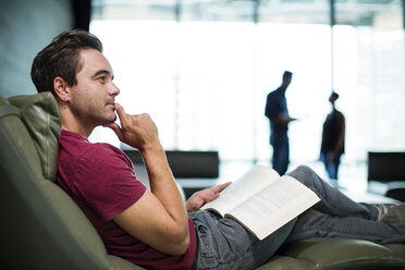 Man in office sitting in armchair, reading a book - ZEF14336