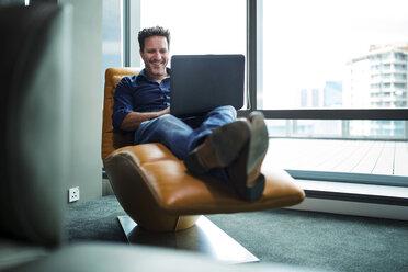 Mature man working in armchair, usiing laptop - ZEF14339