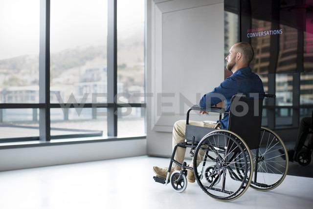 Man in wheelchair looking out of window in office - ZEF14351 - zerocreatives/Westend61