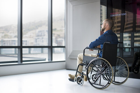 Man in wheelchair looking out of window in office - ZEF14351