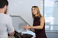 Businesswoman with colleague standing by control screen - ZEF14354