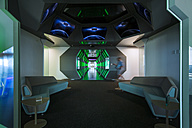 Man with cup of coffee walking in futuristic corridor in modern office - ZEF14369