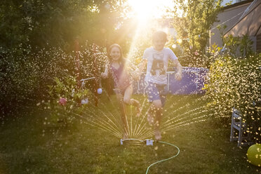 Brother and sister having fun with lawn sprinkler in the garden - SARF03348