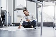 Businessman sitting on the floor of his office looking at construction plan - DIGF02683
