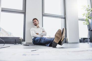 Businessman relaxing on the floor of his office - DIGF02686