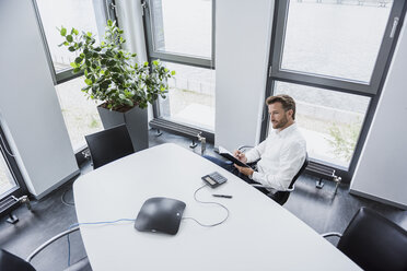 Businessman sitting at meeting table in his office - DIGF02689