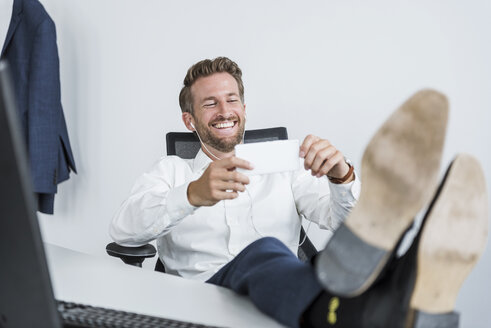 Businessman with earphones sitting at desk with feet up looking at cell phone - DIGF02692
