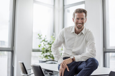 Portrait of laughing businessman sitting on meeting table in the office - DIGF02698
